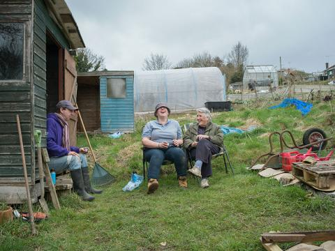Three people laughing while sat having a break in their allotment