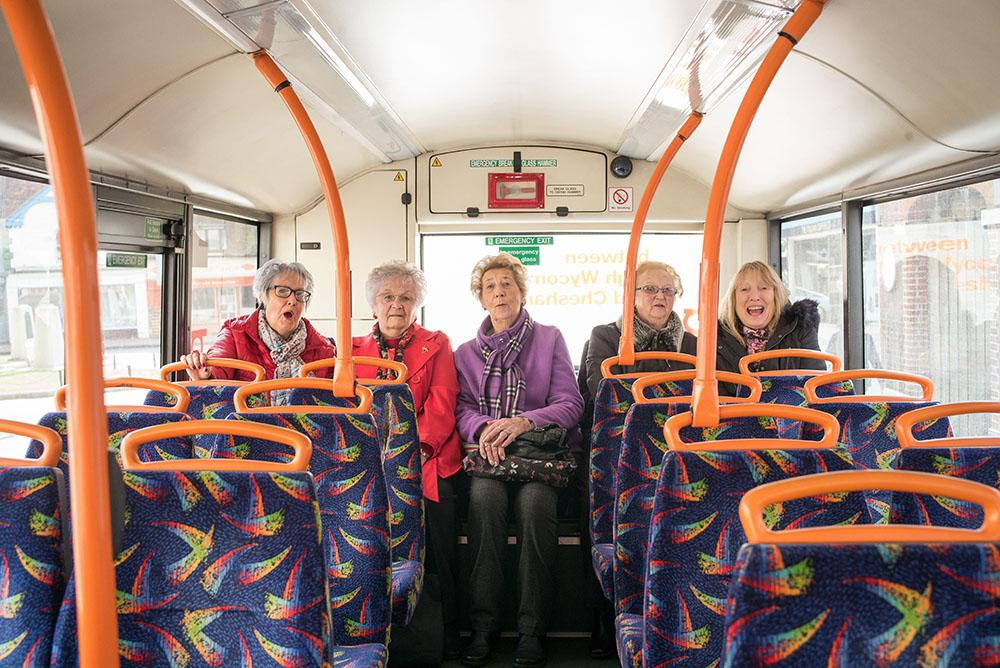 Five elderly women sat at the back of a bus