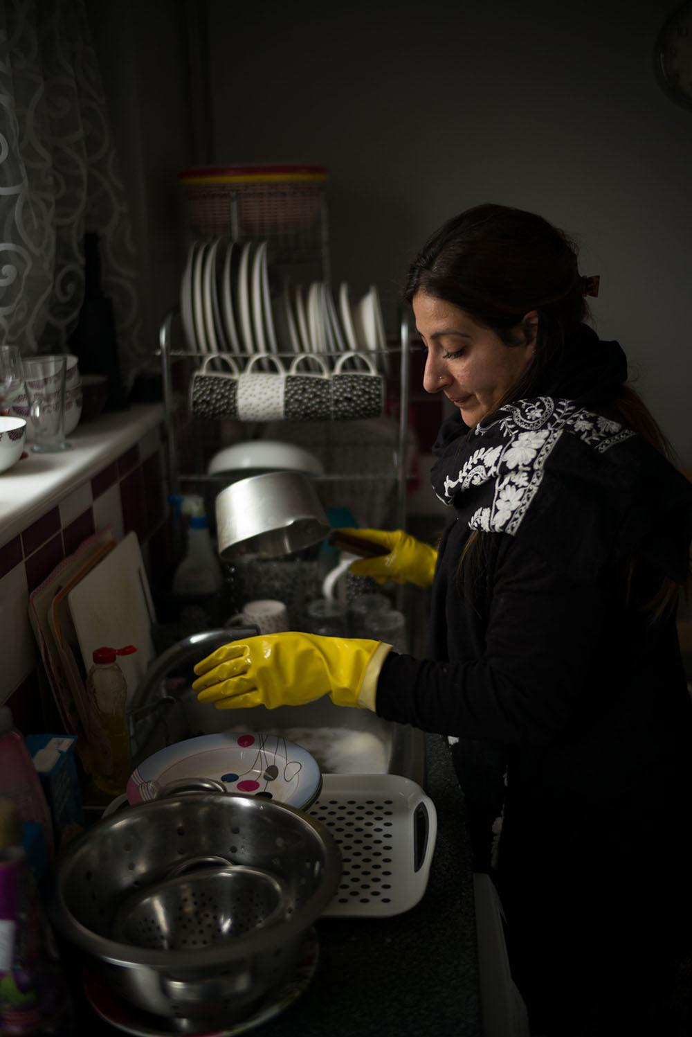 A lady wearing yellow washing up gloves washing pots and pans