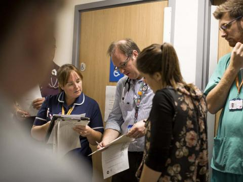 A doctor and a Matron check patient information in a team meeting